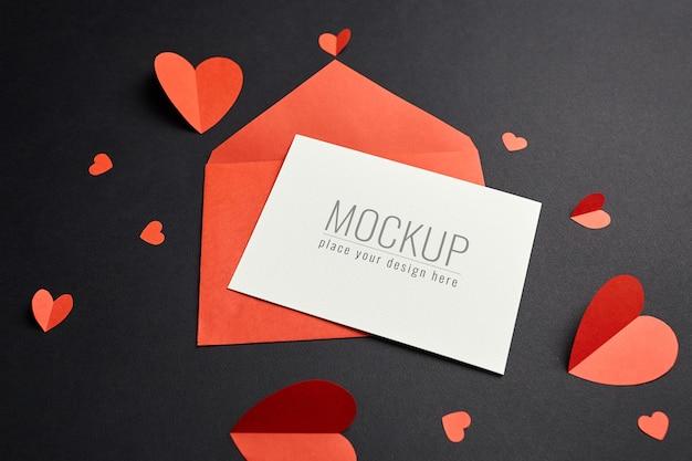 Maquette de carte saint valentin avec enveloppe rouge et coeurs sur papier noir