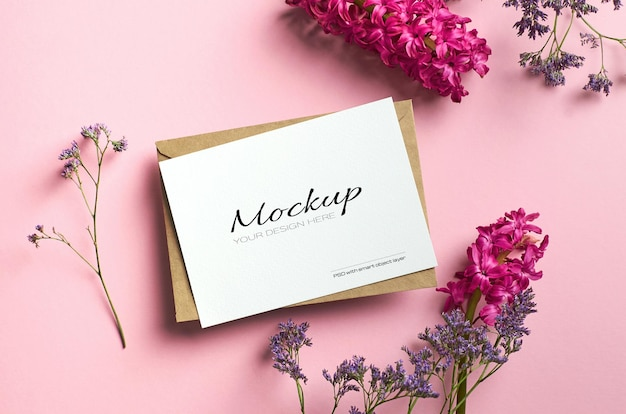 Maquette de carte stationnaire élégante sur papier de couleur rose avec des fleurs de limonium et de jacinthe