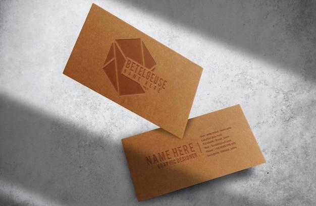 Maquette de carte de visite flottante avec logo en relief en papier brun de luxe en gros plan