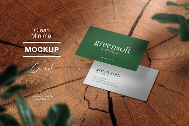 Maquette de carte de visite minimale propre sur le bois et les feuilles