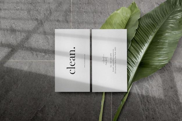 Maquette de carte de visite minimale propre sur du ciment avec des feuilles