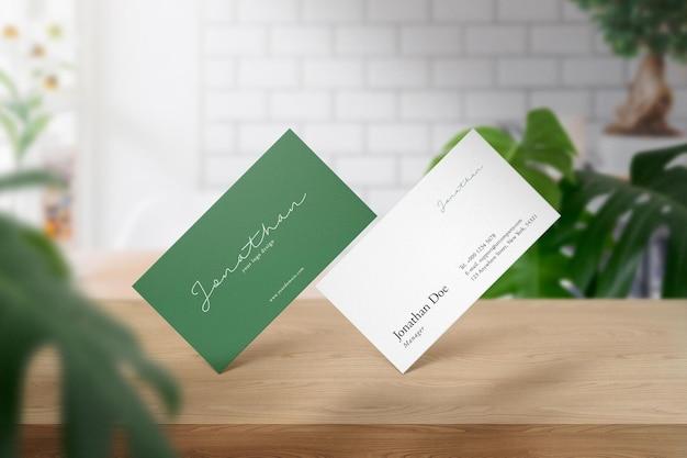 Maquette de carte de visite minimale propre sur la table supérieure avec café blanc