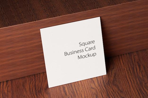 Maquette de carte de visite en papier carré sur table en bois