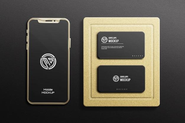 Maquette de carte de visite sombre avec téléphone portable métallique de couleur or