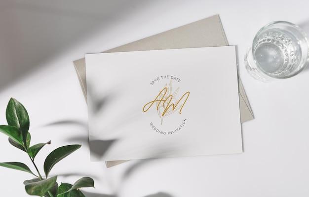 Maquette de carte de voeux blanche avec enveloppe et fleur.