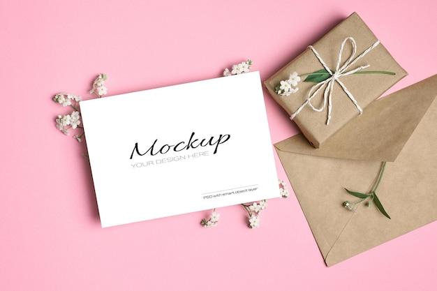 Maquette de carte de voeux avec boîte-cadeau, enveloppe et fleurs de printemps myosotis