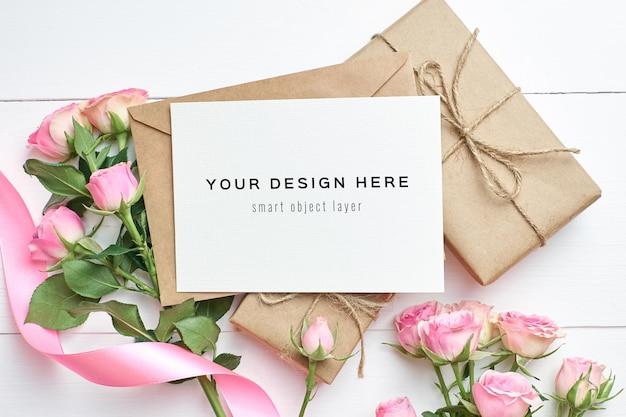 Maquette de carte de voeux avec boîte-cadeau et fleurs roses
