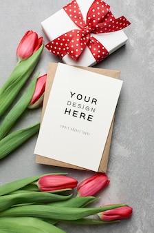 Maquette de carte de voeux avec boîte-cadeau et fleurs de tulipes rouges