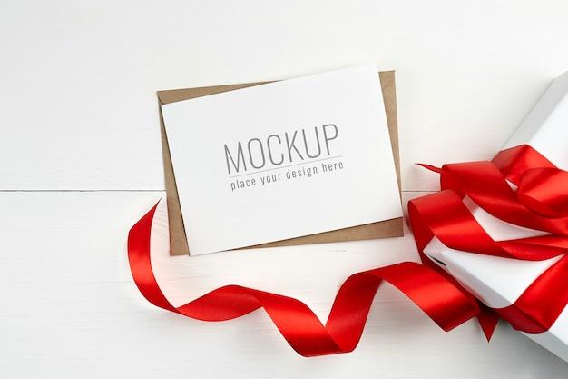 Maquette de carte de voeux avec boîte-cadeau et ruban rouge