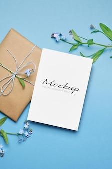 Maquette de carte de voeux avec cadeau et fleurs de myosotis printanières sur bleu