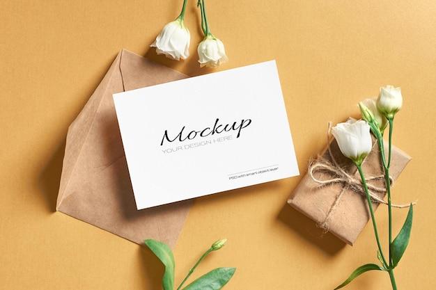 Maquette de carte de voeux avec enveloppe, boîte-cadeau et fleurs d'eustoma blanches
