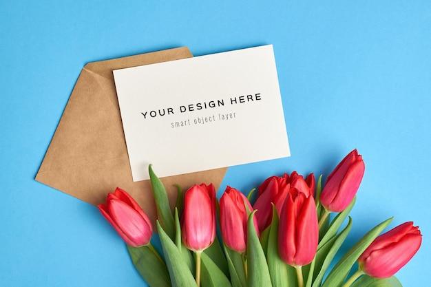 Maquette de carte de voeux avec enveloppe et bouquet de fleurs de tulipes rouges sur fond bleu