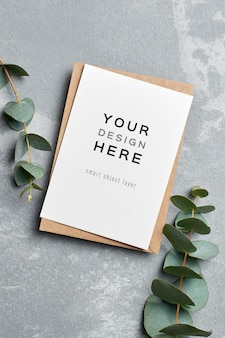 Maquette de carte de voeux avec enveloppe et brindilles d'eucalyptus sur gris