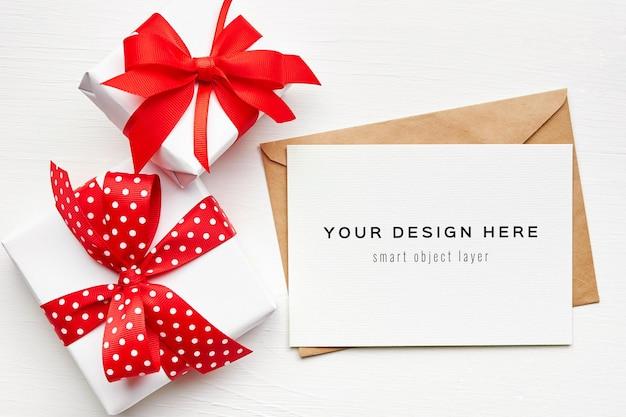 Maquette de carte de voeux avec enveloppe et coffrets cadeaux sur fond blanc