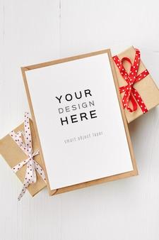 Maquette de carte de voeux avec enveloppe et coffrets cadeaux sur fond de bois blanc