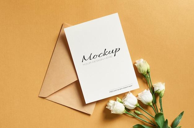 Maquette de carte de voeux avec enveloppe et fleurs d'eustoma blanches sur or