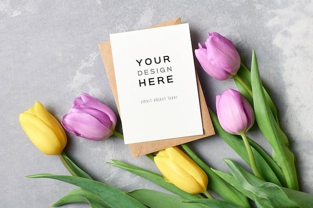 Maquette de carte de voeux avec enveloppe et fleurs de tulipes sur fond gris