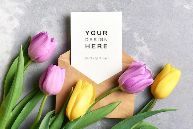 Maquette de carte de voeux avec enveloppe et fleurs de tulipes jaunes et violettes sur gris