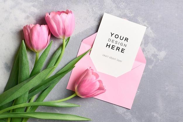 Maquette de carte de voeux avec enveloppe rose et bouquet de fleurs de tulipes