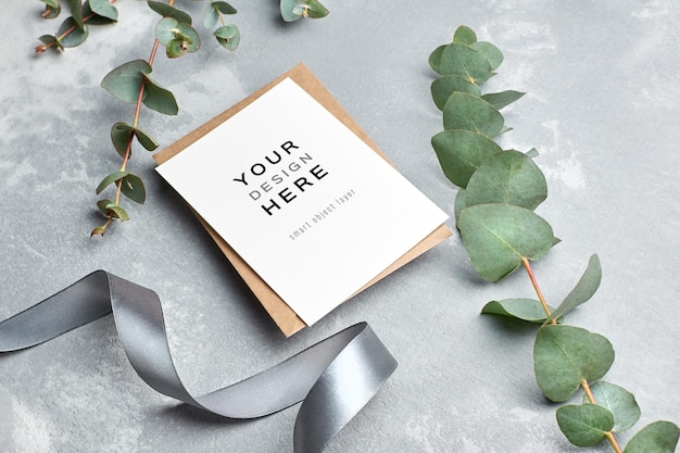 Maquette de carte de voeux avec enveloppe, ruban argenté et brindille d'eucalyptus sur fond gris