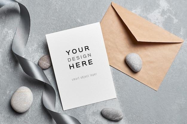 Maquette de carte de voeux avec enveloppe, ruban gris et pierres