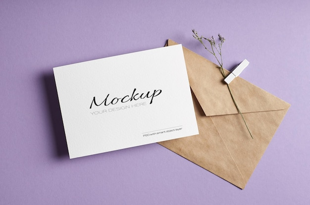Maquette de carte de voeux fixe avec enveloppe et brindille de fleur sèche