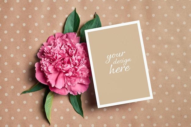 Maquette de carte de voeux avec des fleurs de pivoine rose sur fond de papier kraft