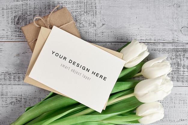 Maquette de carte de voeux avec fleurs de tulipes et boîte-cadeau sur bois