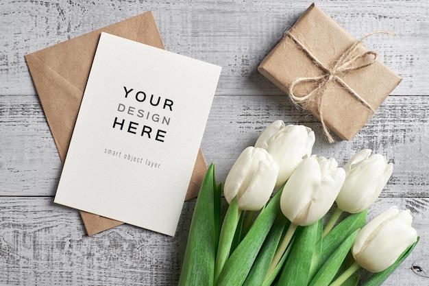 Maquette de carte de voeux avec des fleurs de tulipes et boîte-cadeau sur fond de bois