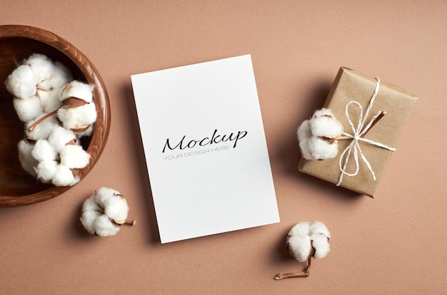 Maquette de carte de voeux ou d'invitation avec boîte-cadeau et décorations de fleurs en coton