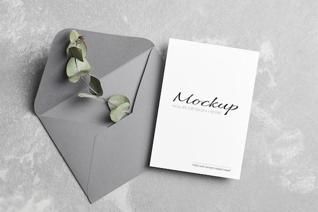 Maquette de carte de voeux ou d'invitation de mariage avec enveloppe et brindille d'eucalyptus sèche