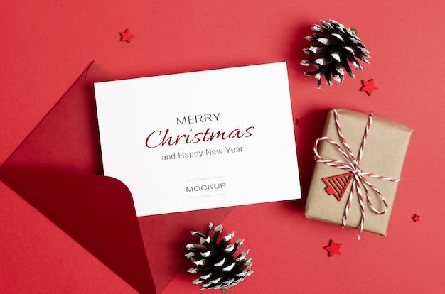 Maquette de carte de voeux ou d'invitation de noël avec enveloppe, boîte-cadeau et décorations de cônes sur rouge