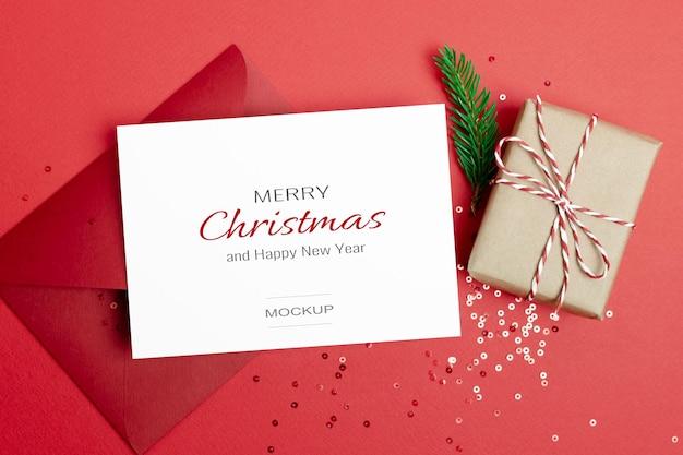 Maquette de carte de voeux ou d'invitation de noël avec enveloppe, boîte-cadeau et décorations festives de confettis sur rouge