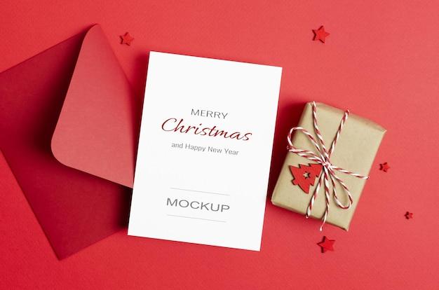 Maquette de carte de voeux ou d'invitation de noël avec enveloppe et boîte-cadeau décorée sur rouge