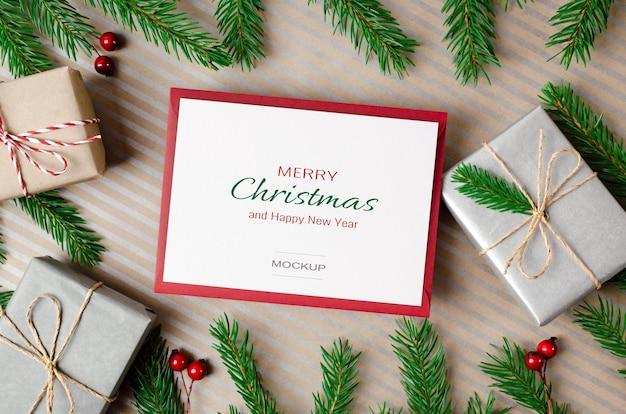 Maquette de carte de voeux joyeux noël avec des coffrets cadeaux et des branches de sapin vert