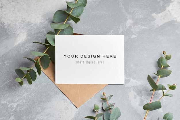 Maquette De Carte De Voeux De Mariage Avec Enveloppe Et Brindilles D'eucalyptus Sur Gris PSD Premium