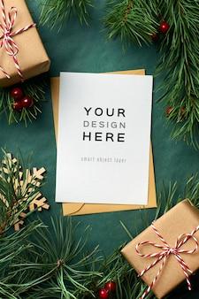 Maquette de carte de voeux de noël avec des branches de pin et des coffrets cadeaux sur fond vert