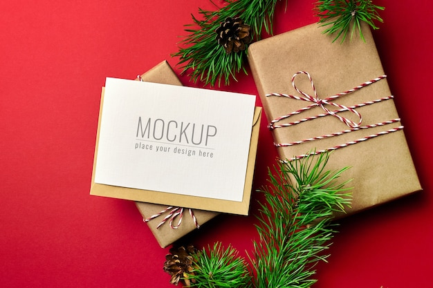 Maquette de carte de voeux de noël avec des coffrets cadeaux et des branches de pin sur fond rouge