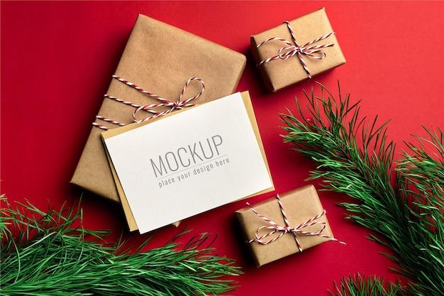Maquette de carte de voeux de noël avec coffrets cadeaux et branches de pin