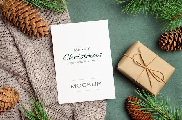Maquette de carte de voeux de noël ou du nouvel an avec boîte-cadeau et branches de sapin avec cônes