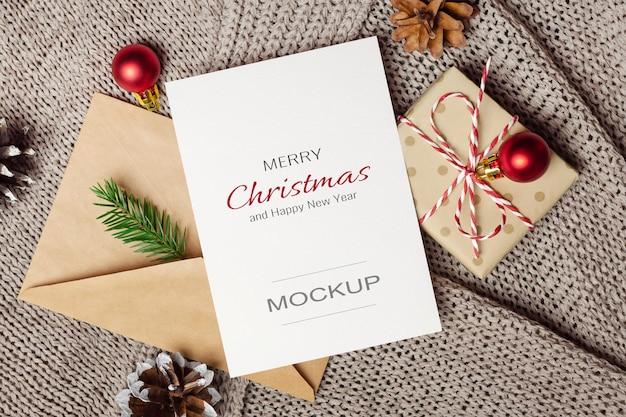 Maquette de carte de voeux de noël ou du nouvel an avec boîte-cadeau, enveloppe et décorations festives