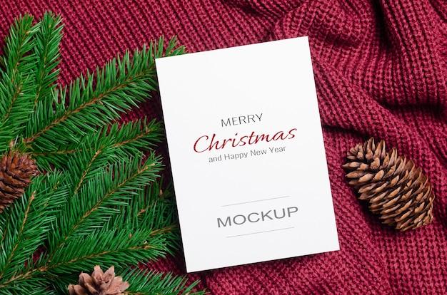 Maquette de carte de voeux de noël ou du nouvel an avec des branches de sapin et des cônes sur fond tricoté