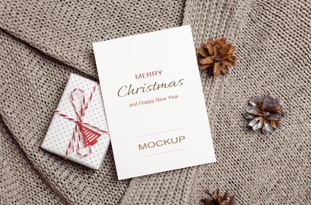 Maquette de carte de voeux de noël ou du nouvel an avec des décorations de boîte-cadeau et de cônes sur fond tricoté