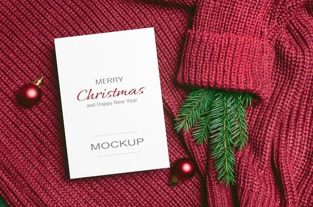 Maquette de carte de voeux de noël ou du nouvel an avec des décorations de boules rouges et une branche de sapin sur fond tricoté
