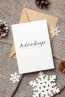 Maquette de carte de voeux de noël ou du nouvel an avec enveloppe, cônes et décorations de flocons de neige en bois