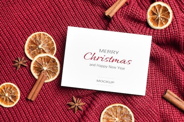 Maquette de carte de voeux de noël ou du nouvel an avec des oranges sèches et des épices sur fond tricoté rouge