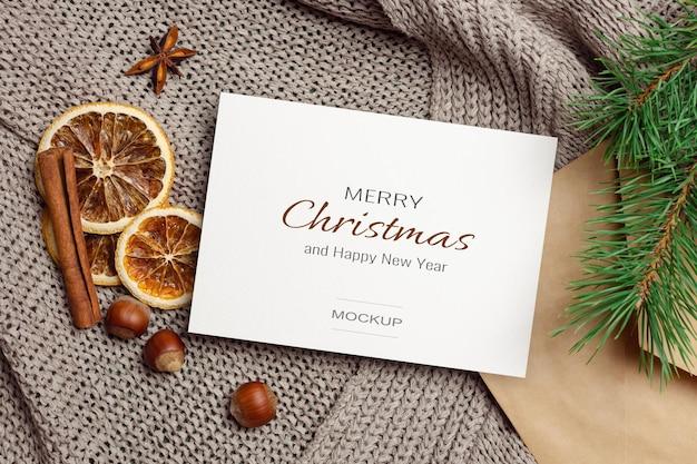 Maquette de carte de voeux de noël avec des oranges sèches, des noix, des épices et des branches de cônes sur fond tricoté