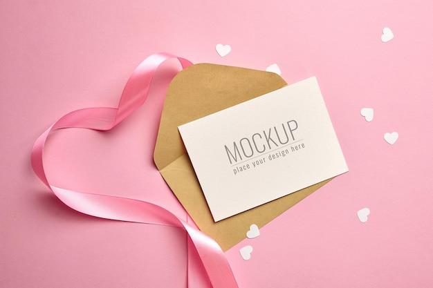 Maquette de carte de voeux avec ruban rose et coeurs en papier blanc