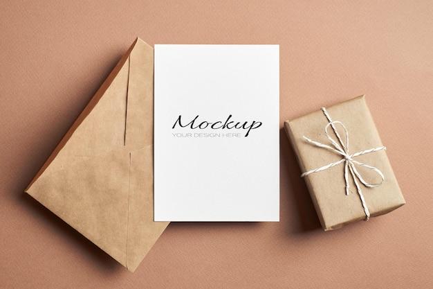 Maquette de carte de voeux stationnaire avec enveloppe artisanale et boîte-cadeau