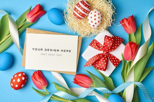 Maquette de carte de voeux de vacances de pâques avec des oeufs colorés, boîte-cadeau et fleurs de tulipes rouges sur bleu